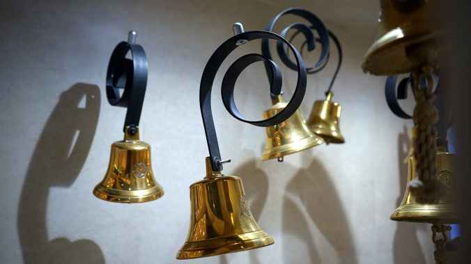 gold colored and black hanging bells near wall